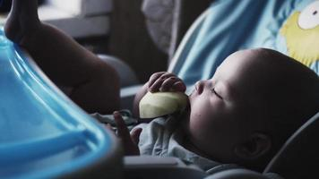 Adorable cute baby sitting at children table eating pear. Feeding. Fruits. Care video
