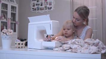 Mother teaching her baby girl how to use a sewing machine video