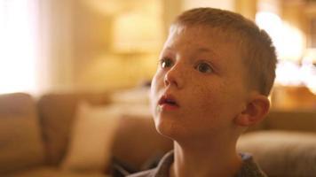 garotinho em casa controlando a televisão com um tablet, close-up