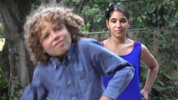 menino e menina dançando em parque público