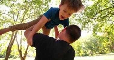 padre e ragazzino che giocano al rallentatore del parco