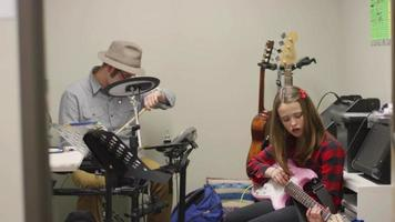 una niña practicando guitarra eléctrica, con su instructor de música video