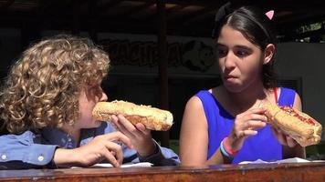 fratelli che mangiano il pranzo con hot dog