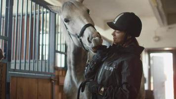 junges Jockey-Mädchen streichelt ein weißes Pferd in einem Stall.