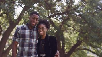 coppia afroamericana sorridente e abbracciando davanti a un albero