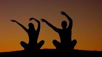 ragazzo e ragazza agitando le mani al tramonto.