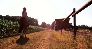 jugendlich Mädchen lächelnd und zurückblickend, während sie ihr Pferd reitet