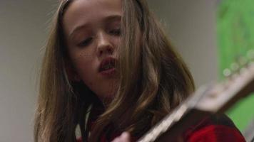 una niña practicando guitarra eléctrica, de cerca