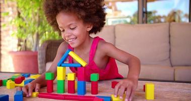 felice bambina afro che gioca con blocchi colorati