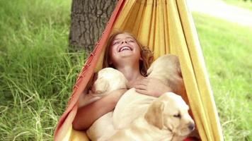 rire fille se balançant dans un hamac avec des chiots au ralenti