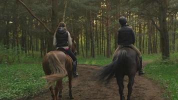 zwei junge Mädchen, die Pferde im Wald reiten