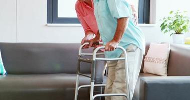 una mujer mayor ayudando a un hombre mayor de pie