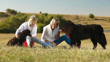 mère et fille nourrissant leurs chiens de Terre-Neuve
