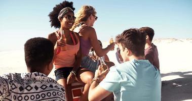 Sonriente niña afro colgando con amigos en la playa