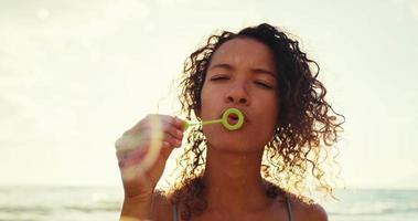 mujer joven que sopla burbujas