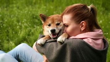 fille et chien shiba inu embrassent