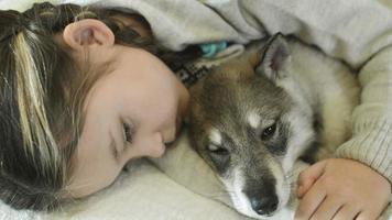 child falls asleep hugging sleeping puppy
