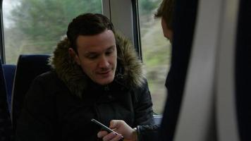 Dos hombres en vagón de tren mirar mensaje de texto filmado en r3d video