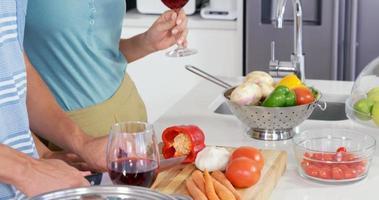 coppia carina prepara il pasto bevendo vino rosso video