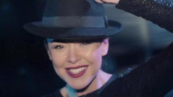 ragazza attraente nella danza superiore nera, gioca con il cappello in discoteca. sorridere sulla fotocamera video