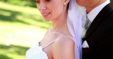Atractivos recién casados sonriendo a la cámara mientras se abrazan