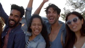 Des amis excités lors d'un road trip acclamant à côté du camping-car