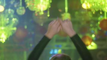 lato posteriore della ragazza dj nella danza superiore nera, alza le mani al giradischi in discoteca video