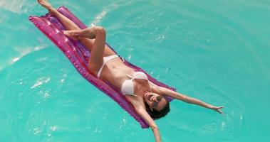 mulher relaxada com óculos de sol no lilo