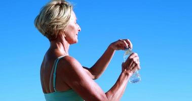 Fit senior woman en pause pour prendre un verre video