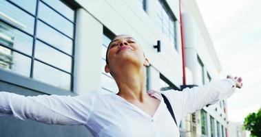 mulher ao ar livre levantando os braços de alegria com a construção de plano de fundo