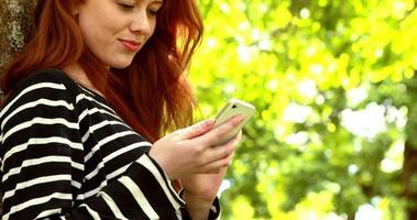 hübsche Rothaarige, die einen Text im Park sendet