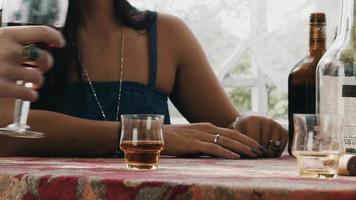 garota sentar no terraço em casa à mesa com bebidas. homem de camisa branca pega copo