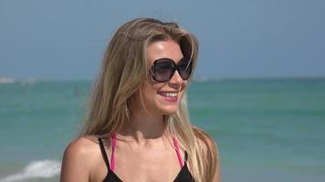 donna con occhiali da sole che cammina all'oceano