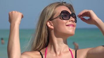 vrouw die met zonnebril bij oceaan loopt
