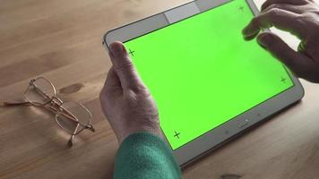 White Tablet PC in an aged woman hands (green screen)