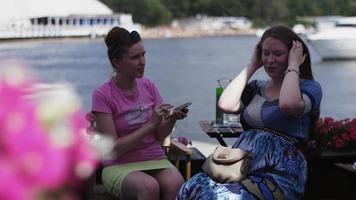 meisje in roze shirt praat met jonge zwangere vrouw. terras aan zee. telefoon