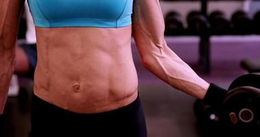 mulher em forma levantando halteres na sessão de ginástica video