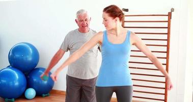 fisioterapista che mostra all'uomo anziano come sollevare pesi