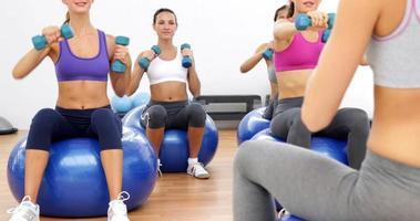 lezione di fitness seduto su palle da ginnastica sollevamento pesi a mano