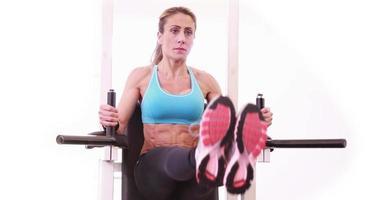 Super Fit Frau macht Leg Ups im Fitnessstudio