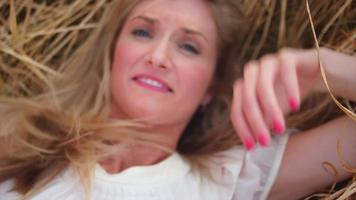 Hermosa mujer rubia tendida en un campo de trigo