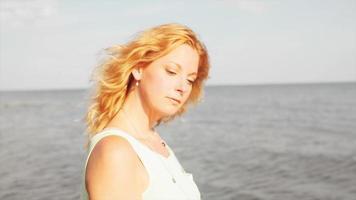 uma mulher em pé na praia ao pôr do sol video