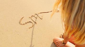 femme blonde écrit dans le sable sur une plage