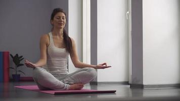 Mujer de yoga meditando y haciendo un símbolo zen con su mano video