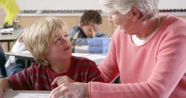 Maestra senior ayudando a joven colegial en clase