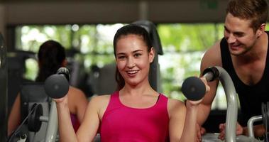 mulher em forma usando máquina de peso