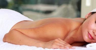 Hermosa morena acostada sobre la camilla de masajes sonriendo a la cámara