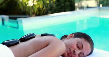 bruna pacifica che ottiene massaggio con pietre calde a bordo piscina