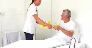enfermeira oferecendo café da manhã para homem sênior relaxando na cama video