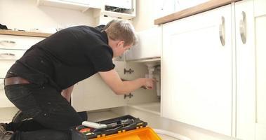 apprendista idraulico che insegna a riparare il lavello della cucina